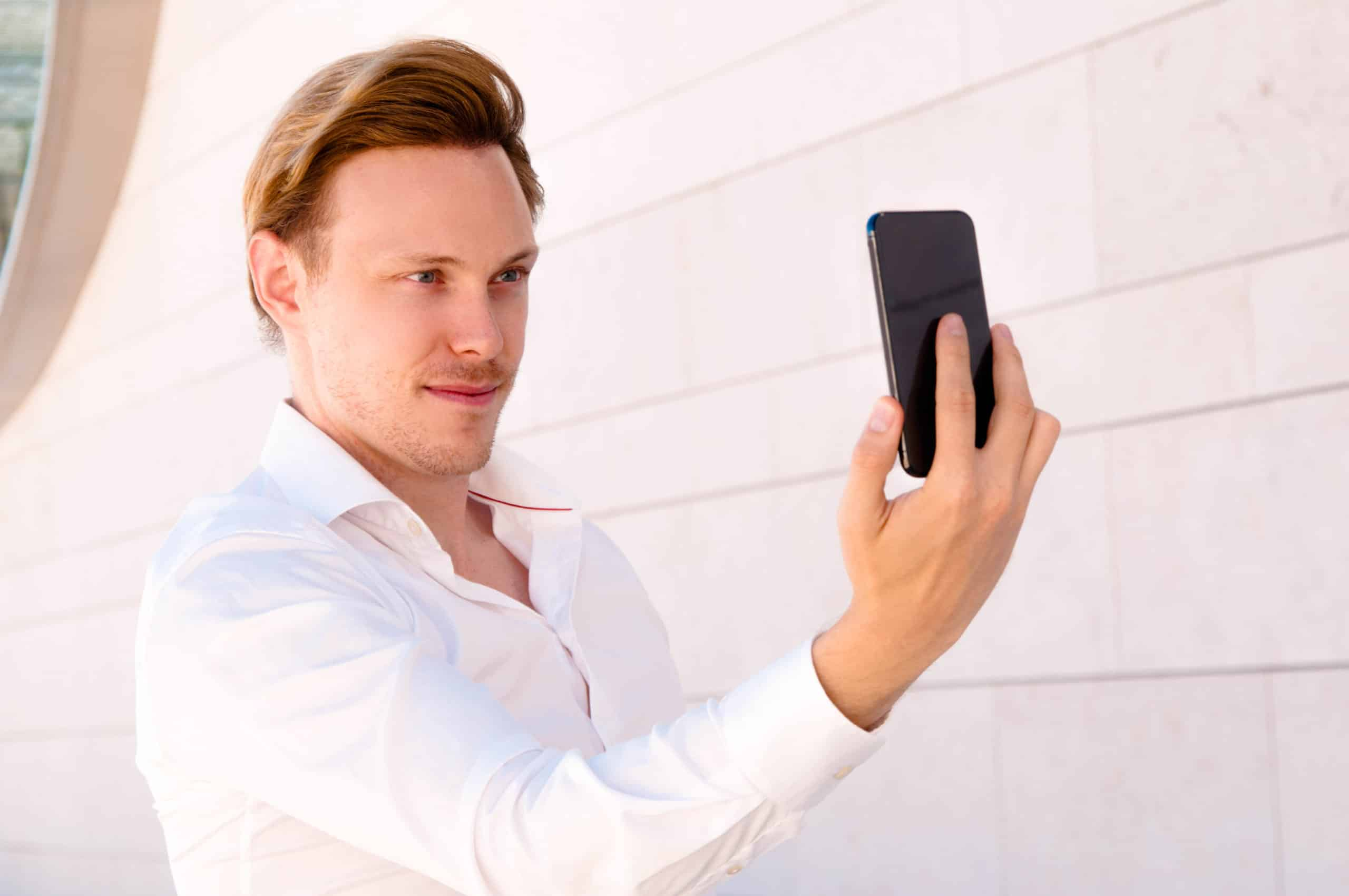 Confident business man posing and taking selfie photo outdoors. Guy posing and standing with building wall in background. Selfie concept.